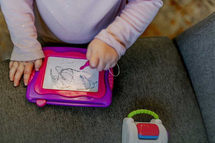 Toddler Playing with Magna Doodle Magnetic Drawing Toy
