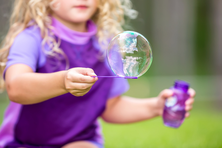 Close-Up of Girl Holding Large Bubble on Purple Wand